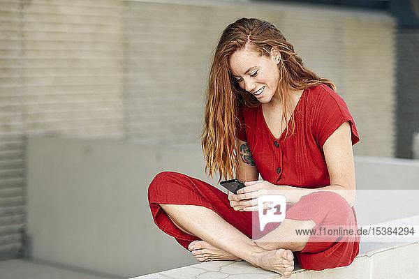 Lächelnde sportliche junge Frau  die eine Pause macht und ihr Smartphone im Freien benutzt