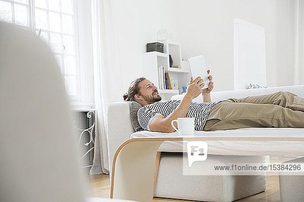 Junger Mann liegt zu Hause auf Couch und benutzt Tablette