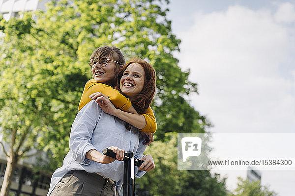 Junge Frau umarmt Freundin auf E-Scooter