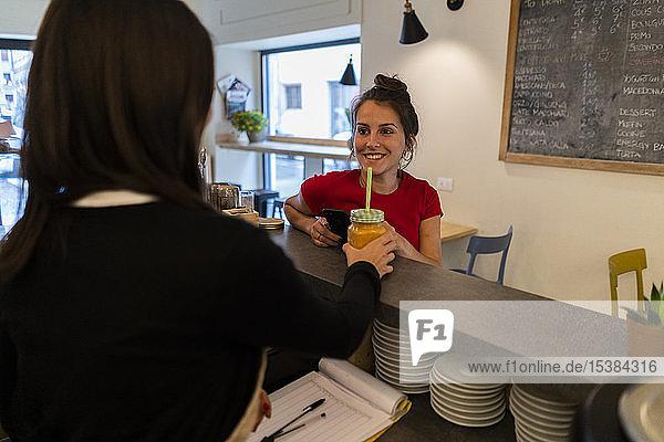 Lächelnde junge Frau an der Theke eines Cafés