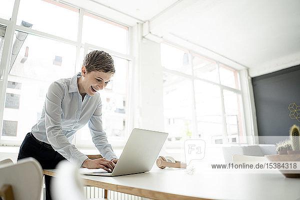 Glückliche Geschäftsfrau benutzt Laptop auf Tisch im Büro