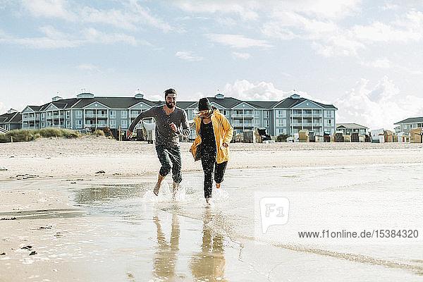 Couple running at the beach in Heiligenhafen