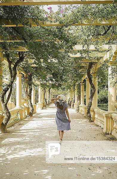 Rückansicht einer Frau  die in einer schönen Passage voller Pflanzen im Park spazieren geht  Aveiro  Portugal