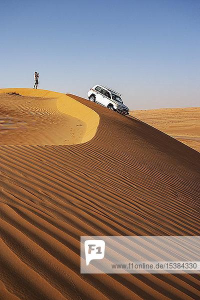 Mann mit Geländewagen,  fotografiert in der Wüste,  Wahiba Sands,  Oman