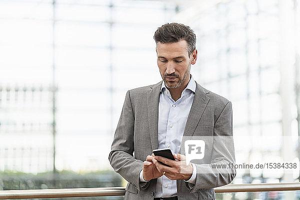 Porträt eines Geschäftsmannes bei der Benutzung eines Mobiltelefons