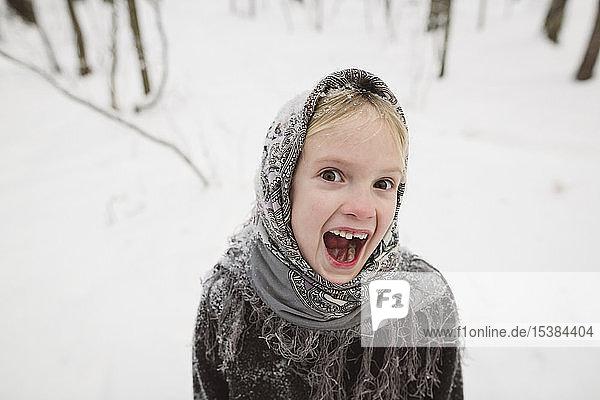 Portrait of screaming little girl in winter forest