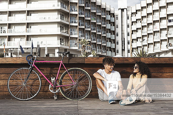 Junges Paar mit Fahrrad sitzt in der Stadt und unterhält sich Junges Paar mit Fahrrad sitzt in der Stadt und unterhält sich