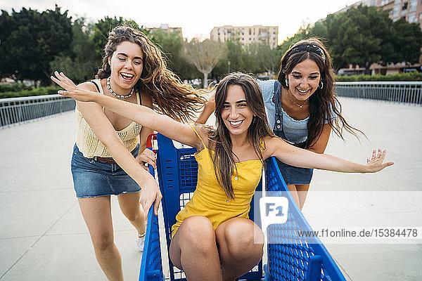 Drei verspielte Freundinnen mit Einkaufswagen in der Stadt