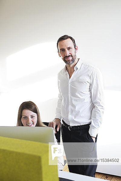 Portrait of confident businessman with employee in office