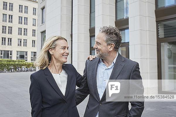 Lächelnder Geschäftsmann und Geschäftsfrau in der Stadt stehen sich gegenüber