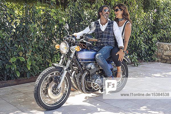Glückliches reifes Paar auf einem Oldtimer-Motorrad