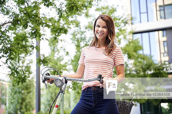 Porträt einer lächelnden Frau mit Fahrrad in der Stadt