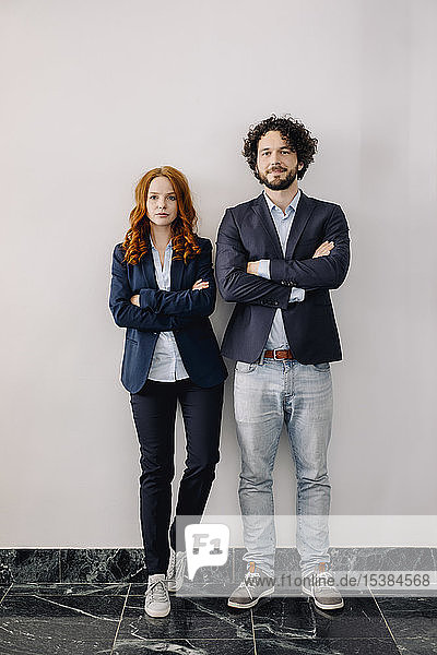 Porträt eines selbstbewussten Geschäftsmannes und einer selbstbewussten Geschäftsfrau  die Seite an Seite stehen