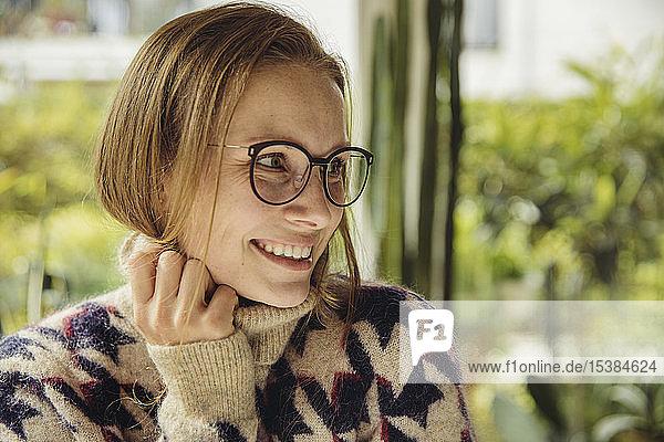 Porträt einer lächelnden jungen Frau mit Brille  die einen flauschigen Pullover trägt und zur Seite schaut