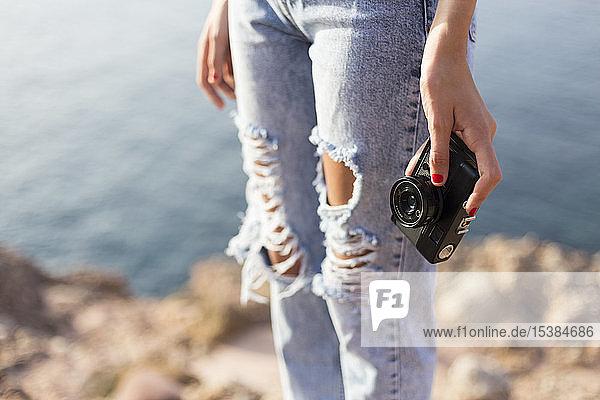 Weiblicher Teenager hält Kamera im Freien