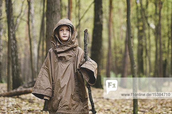 Bildnis eines Jungen in braunem Regenmantel im Herbstwald stehend