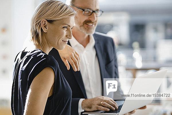 Geschäftsmann und -frau stehen im Café und benutzen einen Laptop