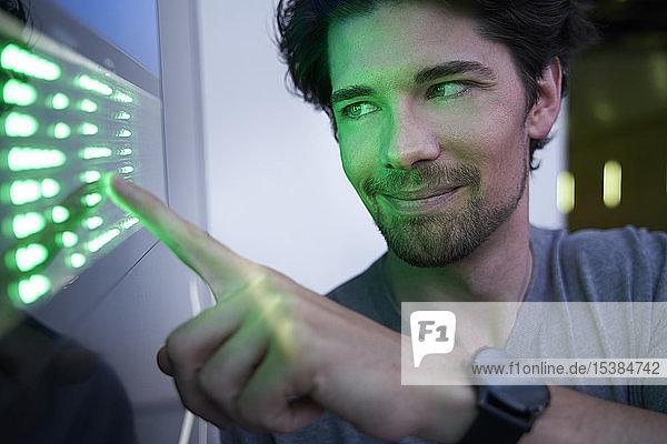Nahaufnahme eines lächelnden Mannes  der einen grün geführten Touchscreen berührt
