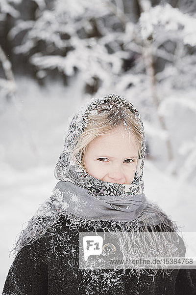 Portrait of snow-covered little girl in winter forest