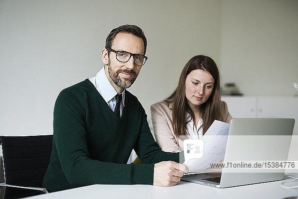 Porträt eines selbstbewussten Geschäftsmannes und Mitarbeiters  der am Schreibtisch im Büro arbeitet