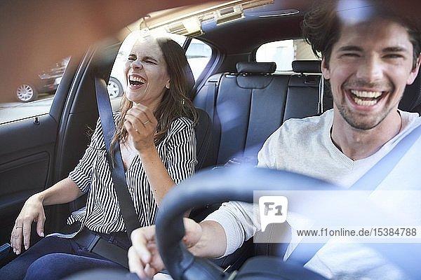 Lachendes Paar in einem Auto mit fahrendem Mann