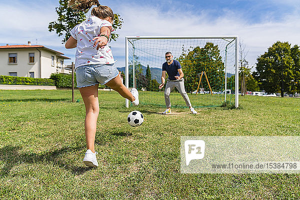 Father and daughter playing football on a meadow