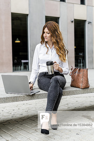 Young businesswoman sitting on bench in the city  working with laptop  drinking coffee