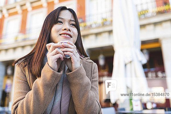 Spanien  Madrid  lächelnde junge Frau in einem Café auf der Plaza Mayor