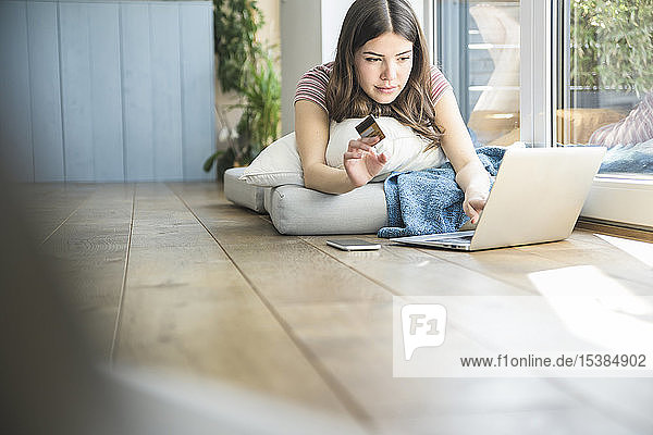 Young woman lying at the window at home shopping online