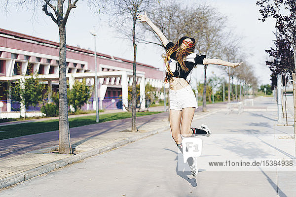 Spain  happy teenage girl jumping on a road
