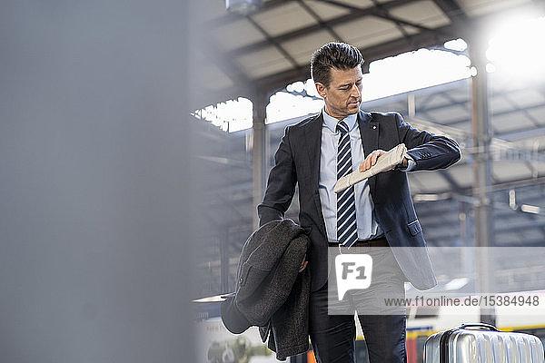 Geschäftsmann  der die Uhrzeit am Bahnhof überprüft