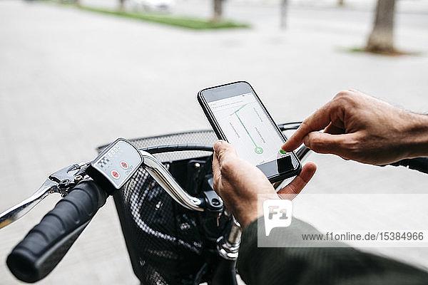 Nahaufnahme eines Mannes mit E-Bike und Smartphone-Navigationssystem
