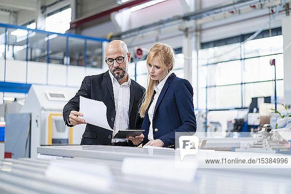 Geschäftsmann und Geschäftsfrau betrachten Papier in einer Fabrik