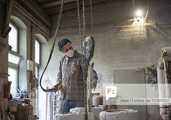 Art foundry  Foundry worker lifting casting mould