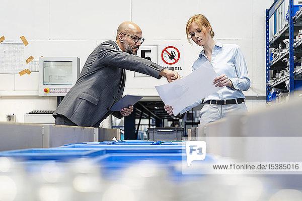 Geschäftsmann und Geschäftsfrau mit Tablette und Plan in der Fabrik