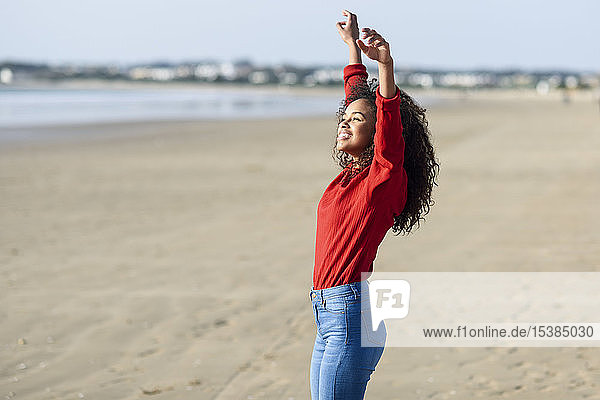 Happy young woman with raised arms standing on the beach