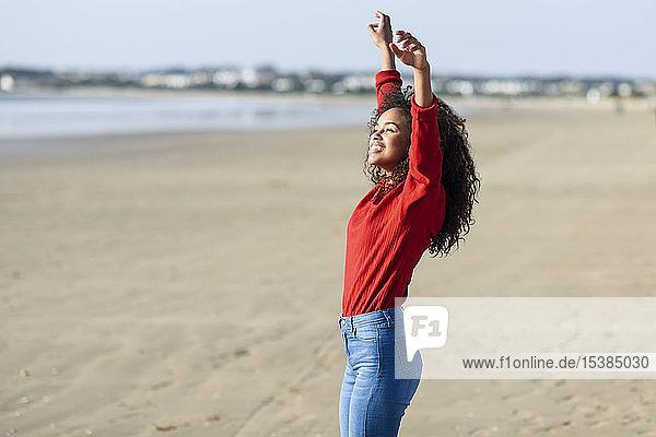 Glückliche junge Frau mit erhobenen Armen am Strand stehend