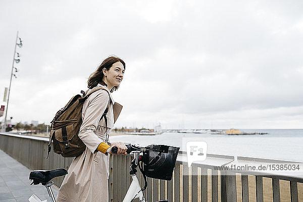 Lächelnde Frau mit E-Bike bei einer Pause an der Strandpromenade