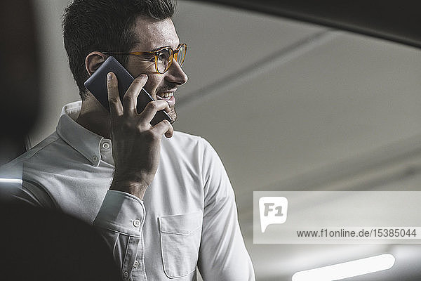 Smiling young man on cell phone at a car