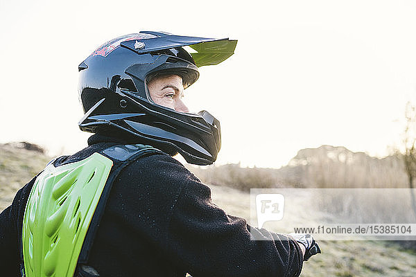 Porträt eines Motocross-Fahrers bei Sonnenuntergang Porträt eines Motocross-Fahrers bei Sonnenuntergang