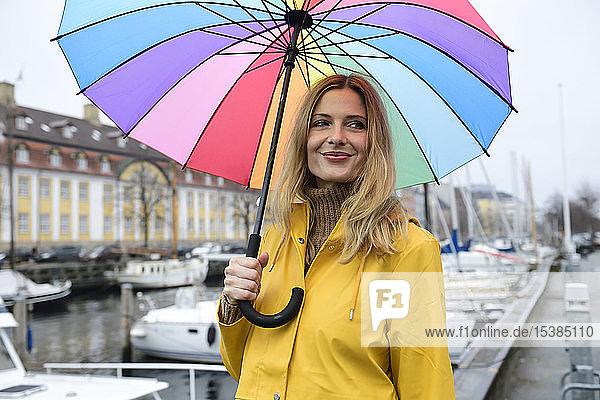 Dänemark  Kopenhagen  lächelnde Frau mit buntem Regenschirm im Stadthafen
