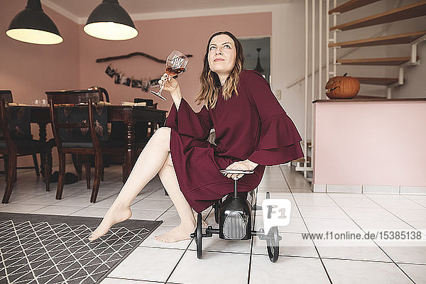 Elegant woman with glass of wine sitting on pedal car at home