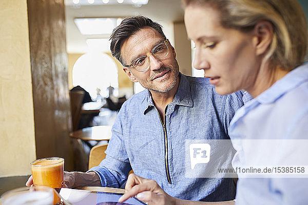 Mann und Frau mit Tablette in einem Cafe
