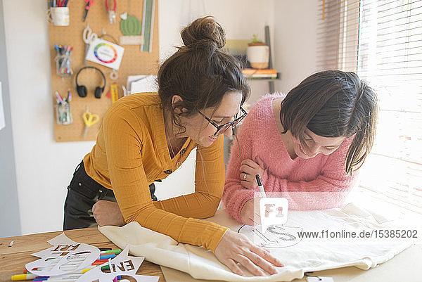Zwei Frauen zeichnen Schablonen für den Druck von Sweatshirts