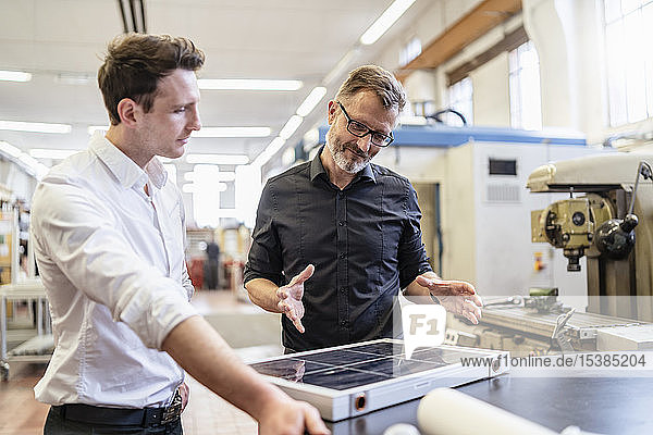 Two colleagues in factory working on solar cell