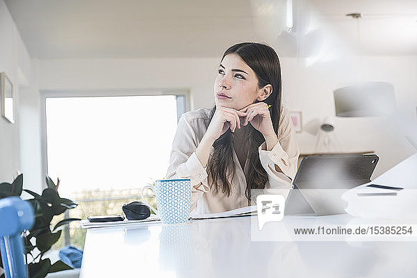 Young woman sitting at table at home looking sideways