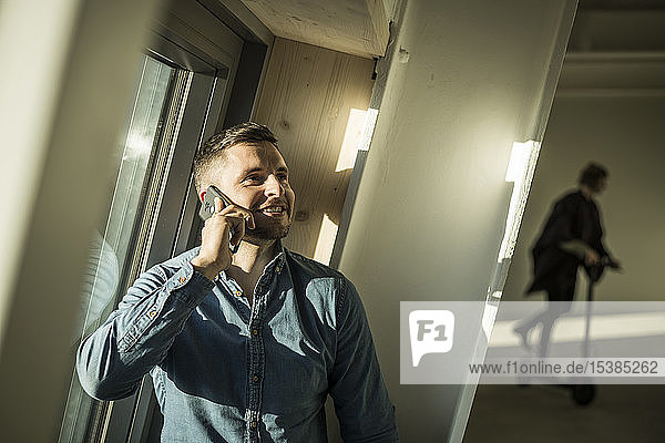 Young businessman talking on the phone  while colleague using kickboard oin background