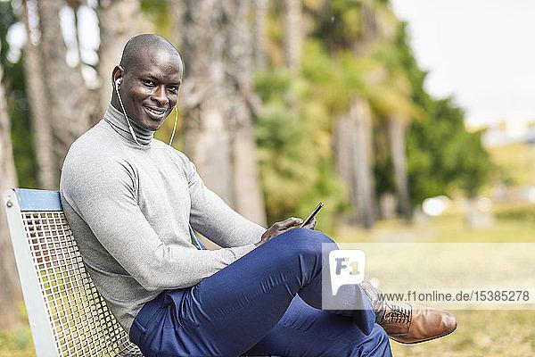Porträt eines lächelnden Geschäftsmannes  der auf einer Bank sitzt und mit Kopfhörern und Smartphone Musik hört
