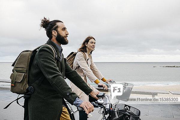 Ein Paar fährt E-Bikes an der Strandpromenade