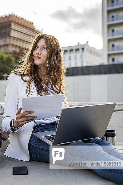 Young businesswoman sitting on stairs in the city  working with laptop  holding document